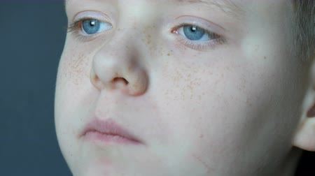 tasting : Freckled blond boy teenager with his blue eyes eating chocolate candy close up view