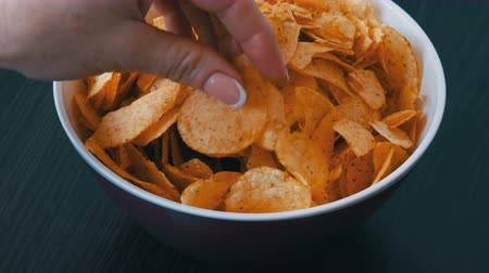 ведущий : Large plate with potato chips on the table. Female hands with beautiful manicure take chips