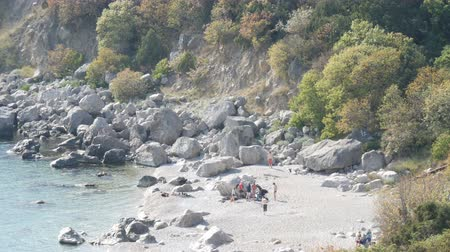 alzarsi : Rocky coast of the Black Sea on which there are few people with tents. Camping in wild places