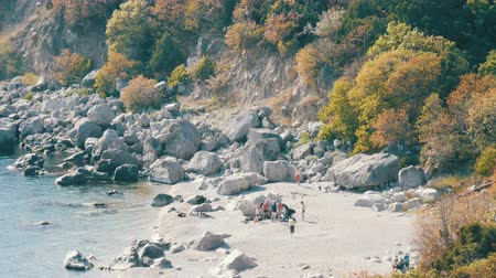 desistir : Rocky coast of the Black Sea on which there are few people with tents. Camping in wild places