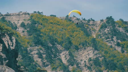 pilots : Yellow paraglider with orange stripes flies in a beautiful mountainous area against the background of gray large rocks Stock Footage