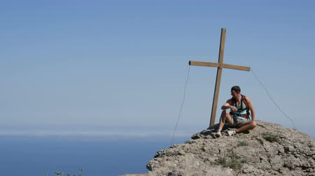 цели : Traveler man with a backpack on his back sits on top of the mountain, with a cross at the peak. Achievement of the goal, motivation to rise. Стоковые видеозаписи