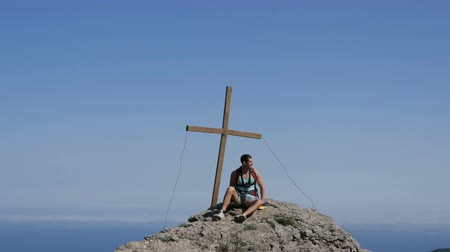 braços levantados : Traveler man with a backpack on his back sits on top of the mountain, with a cross at the peak. Achievement of the goal, motivation to rise. Vídeos