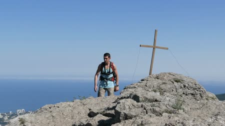 equipamento : Young man walks along the top of the mountain. Achievement of the goal, overcoming oneself, motivation