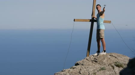 krym : Young man joyfully takes himself off on the action camera, standing on top of the mountain near the cross. Achieving the goal, motivation