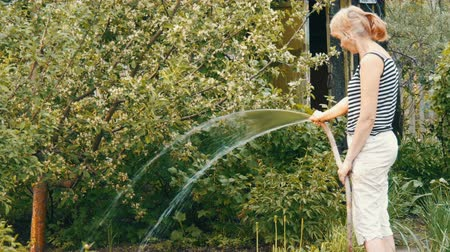 konewka : Woman is watering plants in her garden from a hose