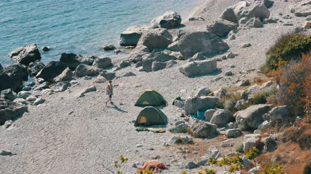 escala : Rocky coast of the Black Sea on which there are few people with tents. Camping in wild places