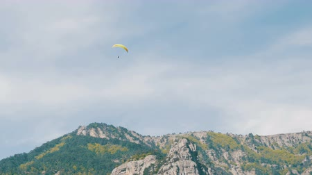 hang gliding : Silhouette of yellow paraglider flying against the sky
