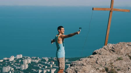 braços levantados : A joyful man in a victorious pose stands at the peak of the mountain shooting himself to the action camera Vídeos