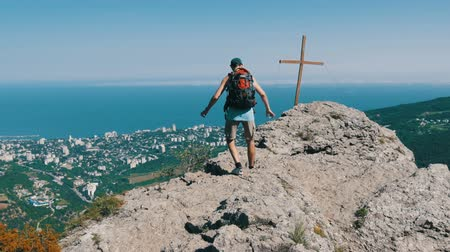 braços levantados : Male traveler with a backpack on his back reaches the top of the mountain, with a cross at the peak. Achievement of the goal, motivation to rise.