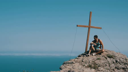 元気づける : Traveler man with a backpack on his back sits on top of the mountain, with a cross at the peak. Achievement of the goal, motivation to rise. 動画素材