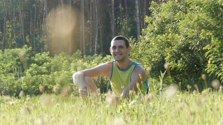 lanscape : Portrait of young handsome cheerful man sitting on the grass in nature in summer on forest background and looking around
