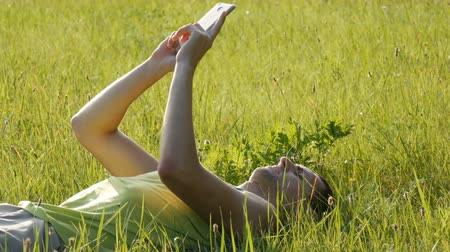 lanscape : Young man is typing something on his smartphone while lying on nature on green grass in summer