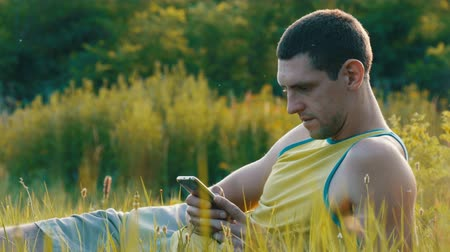lanscape : Young man is typing something on his smartphone while sitting on nature on green grass in summer Stock Footage