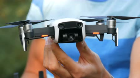 unmanned aircraft : The man in the blue striped shirt holds white drone or quadrocopter close up view