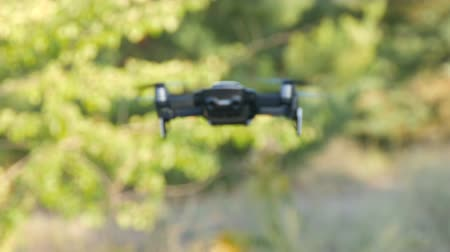 pairar : White or quadrocopter drone in flight against background of green nature, close up view