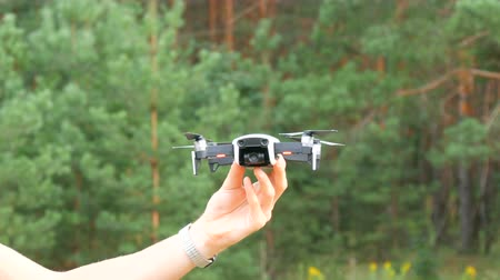 vysílač : A mans hand holds a drone or quadrocopter against the background of a green forest. Future technologies Dostupné videozáznamy