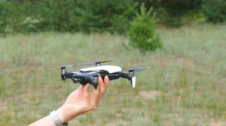 propeller toy : A mans hand holds a drone or quadrocopter against the background of a green forest. Future technologies Stock Footage