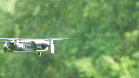 vysílač : A drone or quadrocopter of white color flies in the air against the background of a green forest. Future technologies Dostupné videozáznamy