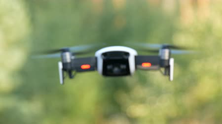 landing field : White or quadrocopter drone in flight against background of green nature, close up view