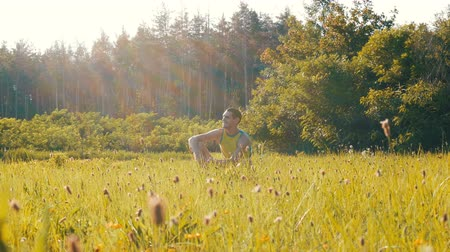 íngreme : Cheerful young man sits on a green grass in summer and smiles Stock Footage