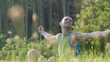 eski : Young man sitting on nature in grass happy enjoying life and smiling Stok Video