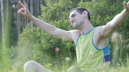 lanscape : Young man sitting on nature in grass happy enjoying life and smiling Stock Footage