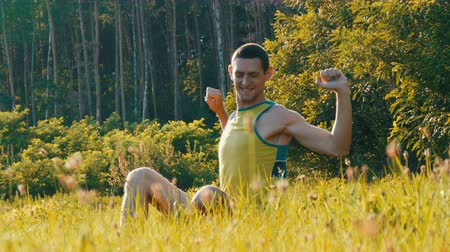 lanscape : Cheerful young man sits on a green grass in summer and smiles Stock Footage