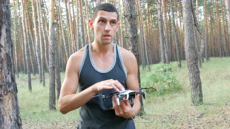 antennák : Cute tall man launches drone or quadrocopter in the woods
