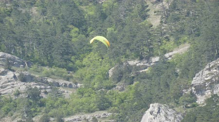hang gliding : Yellow paraglider with orange stripes flies in a beautiful mountainous area against the background of gray large rocks Stock Footage
