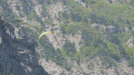 hang gliding : Yellow paraglider flies against a background of green rocky Crimean mountains