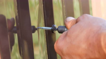 tutturma : Hand screwdriver and screws cut into the iron sheet metal close view. Mens hands repairing fence