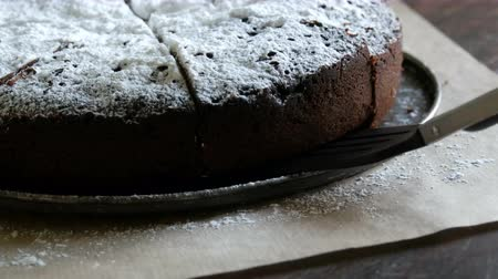 baked pudding : Special tongs for baking take piece of freshly baked chocolate brownie cake powdered with icing sugar