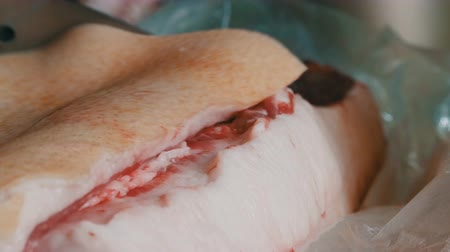 smalec : Male butcher cuts a large piece of fresh pork meat with a large knife. Pork lard with meat and skin close up view