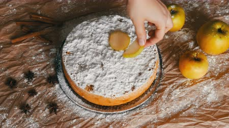 american cuisine : Female hand puts apple slices on delicious traditional freshly baked homemade gingerbread apple pie Charlotte richly powdered sugar top view Stock Footage