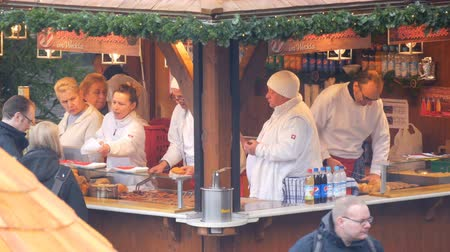 nuremberg : Nuremberg, Germany - December 1, 2018: Kiosk on European Christmas market, which sells national German sausages. Crowd of people queuing for food Stock Footage
