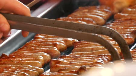 nuremberg : Women grill lot of delicious fresh German sausages. A large number of Nuremberg sausages near fresh buns are prepared on the Christmas food market close up view