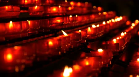 высокое разрешение : Burning memorial candles in Catholic church. Row of christian prayer red round votive candles burn in the dark. Prayer lighting Sacrificial Candles close up. Celebrating christmas in Cathedral