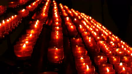 Row of christian prayer red round votive candles burn in the dark. Prayer lighting Sacrificial Candles. Burning memorial candles in Catholic church. Celebrating christmas in Cathedral Stock Footage