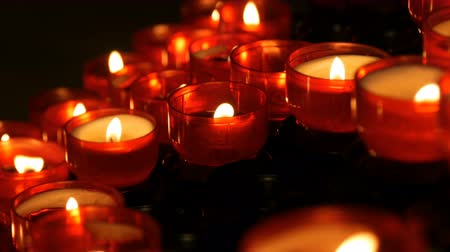 освещенный : Row of christian prayer red round votive candles burn in the dark. Prayer lighting Sacrificial Candles close up. Burning memorial candles in Catholic church. Celebrating christmas in Cathedral