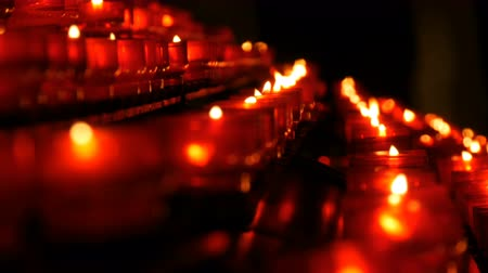 Burning memorial candles in Catholic church. Row of christian prayer red round votive candles burn in the dark. Prayer lighting Sacrificial Candles close up. Celebrating christmas in Cathedral