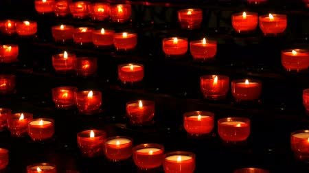 christmas background : Row of christian prayer red round votive candles burn in the dark. Prayer lighting Sacrificial Candles. Burning memorial candles in the Catholic church. Celebrating christmas in Cathedral
