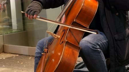 húr : Street musician playing the cello. Cellist in gloves gently bows strings Stock mozgókép