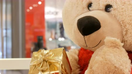szépia : Funny toy Teddy bear move holding in his hand a box with a Christmas gift close up. Christmas decor in the mall