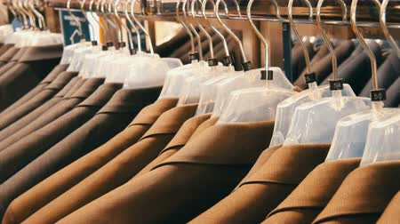 vállfa : Brown and gray mens jackets hang on hangers in the mens clothing store in the mall. A huge range of mens suits on hangers in shopping center close up view