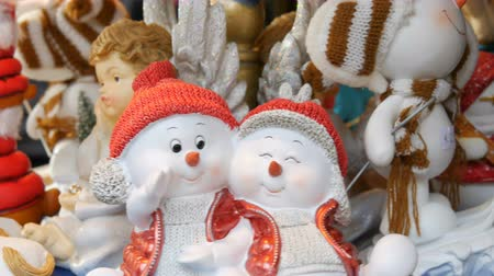 Christmas and New Years toy statues in the form of angels, deer, snowmen in Santa Claus hats that are spinning on counter of the Christmas market