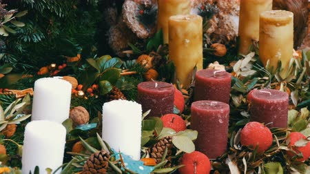 падуб : Many large multi-colored Christmas thick wax candles standing in holly and spruce. The spirit of Christmas and the new year. Scenery for a holiday in the market on eve of Christmas