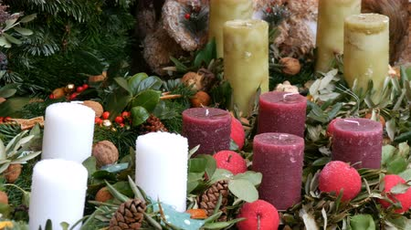 azevinho : Many large multi-colored Christmas thick wax candles standing in holly and spruce. The spirit of Christmas and the new year. Scenery for a holiday in the market on eve of Christmas