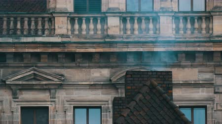 flue shot : Smoke comes from the old brick chimney of the house. The pipe on the roof in historical center of Nuremberg Stock Footage