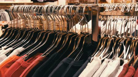 centímetro : A large number of womens clothing of different colors hangs on hangers and lies on the shelves in a clothing store of shopping center or mall. The problem of consumerism Vídeos